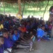 Children sitting under the grass school hut to learn.
