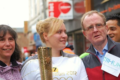 Me holding the olympic torch in 2012 with my mam and dad