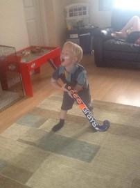 James impersonating his elder siblings playing hockey.