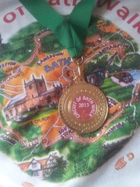 My medal from completing the full 20-mile circuit, set against the background of the T-shirt purchased from the charity.