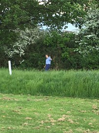 charlie using his club as a weed whacker during a practice round