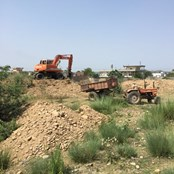 Diggers working on the land to ensure it is flat enough before foundations are laid.