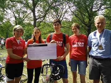 Louise (left) after riding 100 miles with Shelter cheque