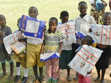 Children receiving mosquito nets to protect them from malaria