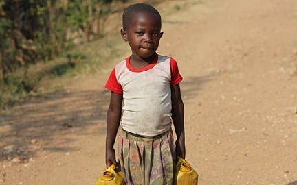 A girl carrying a jerry can