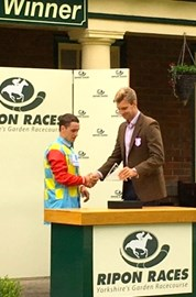 """Alexander presenting the prize to the winning jockey in 'The Alison Memorial for Yorkshire Kidney Research Fillies Handicap Stakes"""""""