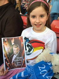 Ella at Old Trafford with her birthday card signed by Robbie Williams at the match!