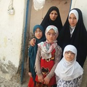 Rahaf, her three sisters and mother standing outside their damaged house.