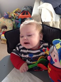 Trying really hard to hold my toy whilst in my special Bee chair (not my favourite place to be!)