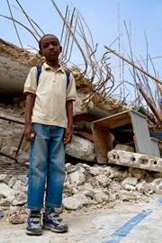 Haitian child next to destroyed building