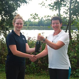 Hilary presents a bottle of Champagne to our top fundraiser from the 2015 event