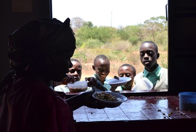 Children receiving lunch from the kitchen built by African Promise