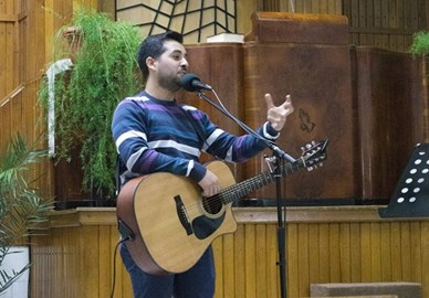 Zozo playing guitar at a worship event